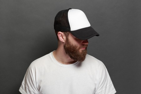 Hipster handsome male model with beard wearing white blank t-shirt and a baseball cap with space