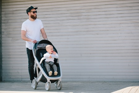 Father walking with a stroller and a baby in the city streets Stockfoto