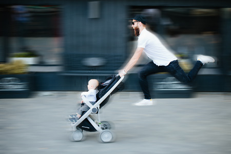 Father running with a baby in a stroller along the city streets with motion blur Stock Photo