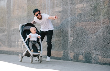 Father walking with a stroller and a baby in the city streets Stock Photo