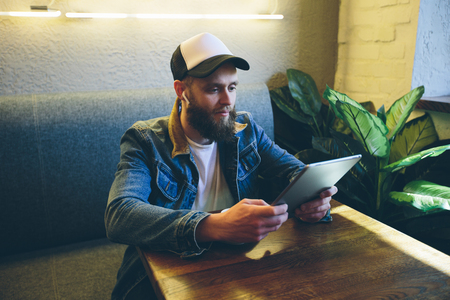 Hipster man with sport in-ear wireless headphones listening to music and usindg a tablet pc Stock Photo