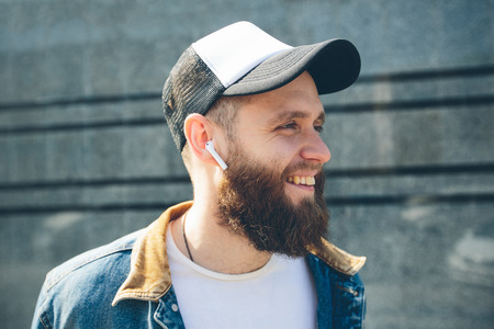 Hipster man with sport in-ear wireless headphones listening to music and relaxing