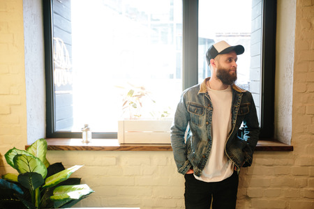 Hipster with beard standing next to a window