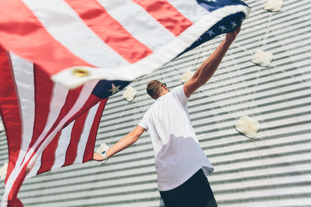 Happy hipster man holding American or USA flag. He is wearing casual clothes.