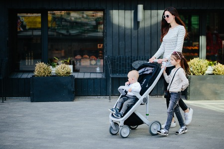 Mother walking with a baby and a stroller in the city street
