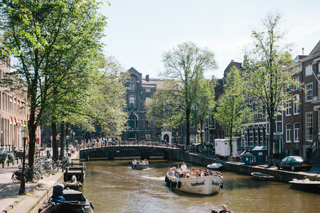 NETHERLANDS, AMSTERDAM - JUNE: 15,2017: Veiw on the bridge through the river channel with a touring boat, picture of canals in Amsterdam Editorial