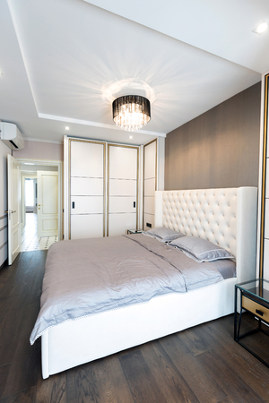 Modern bedroom interior with a big bed and a Chandelier Stock Photo