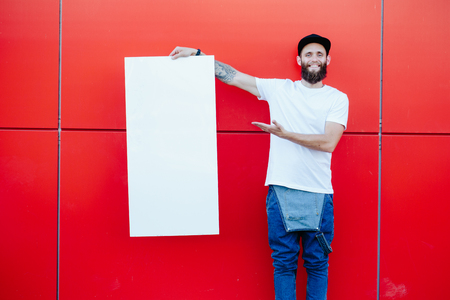 Hipster man holding a poster Stock Photo