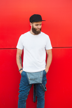 Hipster handsome male model with beard wearing white blank t-shirt and a baseball cap with space for your logo