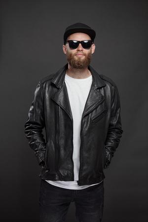 Mann mit Leder-Bikerjacke oder asymmetrischer Reißverschlussjacke mit schwarzer Mütze, Jeans und Sonnenbrille. Hübscher Hipster-Mann über grauem Hintergrund