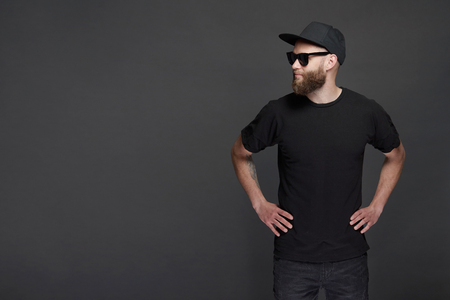Hipster handsome male model with beard wearing black blank baseball cap with space for your logo Zdjęcie Seryjne
