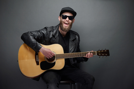 Gitarrist, der im Musikstudio singt. Hipster-Gitarrist mit Bart und schwarzer Kleidung, der Akustikgitarre spielt Standard-Bild