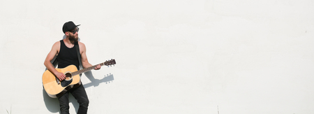 Guitar player outside over white wall