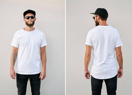 Hipster hübsches männliches Model mit Bart trägt weißes leeres T-Shirt und eine Baseballmütze mit Platz für Ihr Logo oder Design im lässigen urbanen Stil. Rück- und Vorderansicht Standard-Bild