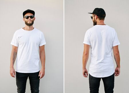 Hipster handsome male model with beard wearing white blank t-shirt and a baseball cap with space for your logo or design in casual urban style. Back and front view Фото со стока