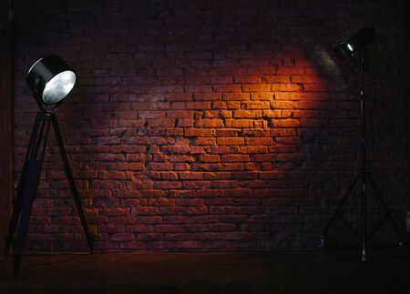 Old retro red brick wall being lit by a stage light bulb light. Constant light modifier projecting light on it 写真素材