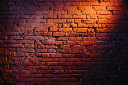 Old retro red brick wall being lit by a stage light bulb light. Constant light modifier projecting light on it Фото со стока