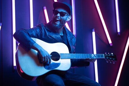Singer and guitar player singing on a stage with neon lights. He is a rocker and he is wearing leather biker jacket or asymmetric zip jacket with black cap, jeans