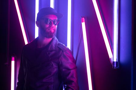 Hipster handsome man on the city streets being illuminated by neon signs. He is wearing leather biker jacket or asymmetric zip jacket with black cap, jeans and sunglasses. Reklamní fotografie