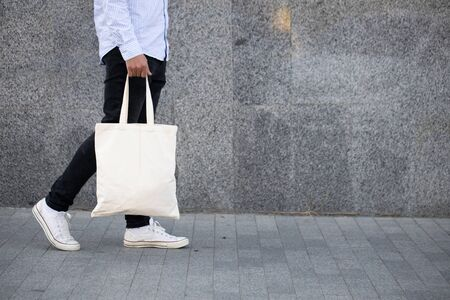 Young man holding white textile eco bag against urban city background. Ecology or environment protection concept. White eco bag for mock up. Foto de archivo
