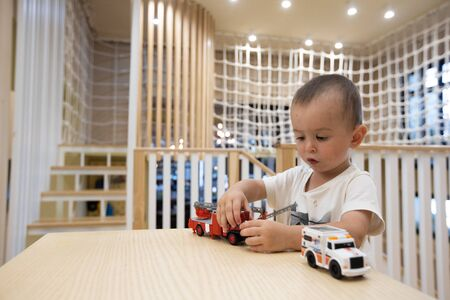 Child boy playing with toy cars