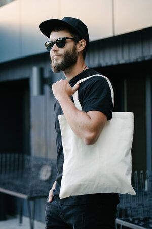 Young man holding white textile eco bag against urban city background. Ecology or environment protection concept. White eco bag for mock up. Reklamní fotografie