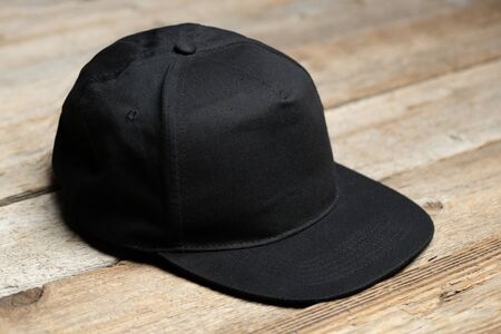 Black baseball cap for mock up or your logo over wooden background