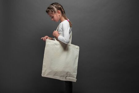 Kid girl holding white textile eco bag against gray background. Ecology or environment protection concept. White eco bag for mock up