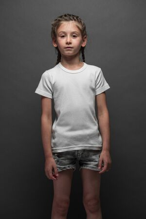 Kid girl wearing white t-shirt with space for your logo or design over gray background