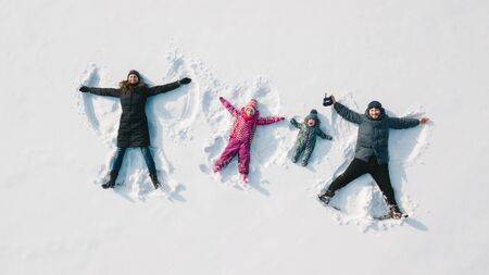 Family making a snow angel. Aerial view. Mother and father and chilren making a snow angel Reklamní fotografie