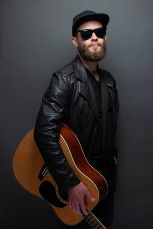 Singer and guitar player singing on a stage. He is a rocker and he is wearing leather biker jacket or asymmetric zip jacket with black cap, jeans. Stock Photo