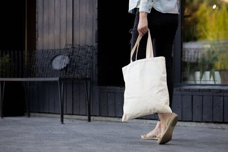 Woman holding an eco bag. Ecology or environment protection concept. White eco bag for mock up. Reklamní fotografie