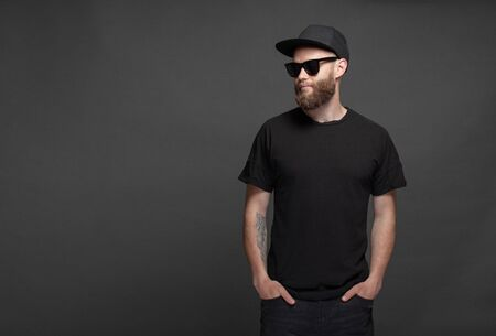 Hipster handsome male model with beard wearing black blank t-shirt with space for your logo or design