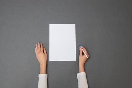 White sheet of paper for your text. Woman holding an empty sheet of paper over gray texture. Overhead view Reklamní fotografie