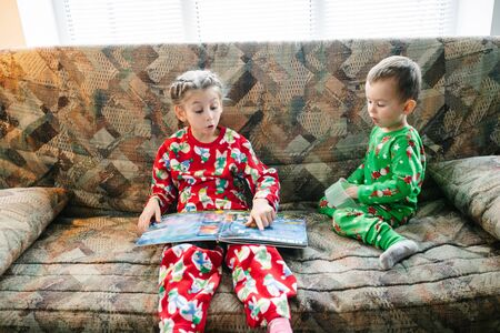 Children are reading a book next to a christmas tree wearing pajamas Reklamní fotografie