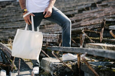 Young man holding white textile eco bag against urban city background. Ecology or environment protection concept. White eco bag for mock up. Stockfoto