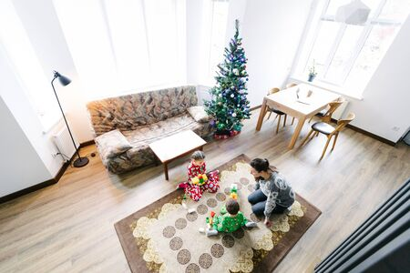 Children with mother playing indoors next to a christmas tree