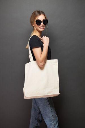 Young woman holding white textile eco bag against gray background. Ecology or environment protection concept. White eco bag for mock up.