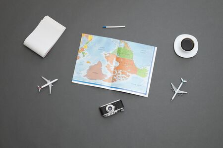 World map over gray table with toy airplanesand a coffee cup Reklamní fotografie