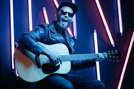Singer and guitar player singing on a stage with neon lights. He is a rocker and he is wearing leather biker jacket or asymmetric zip jacket with black cap, jeans.