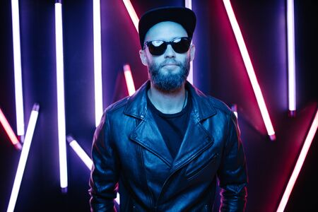 Hipster handsome man on the city streets being illuminated by neon signs. He is wearing leather biker jacket or asymmetric zip jacket with black cap, jeans and sunglasses. Stock Photo
