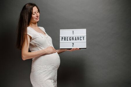 Pregnant woman portrait. She is holding a belly and smiling Standard-Bild - 134475834