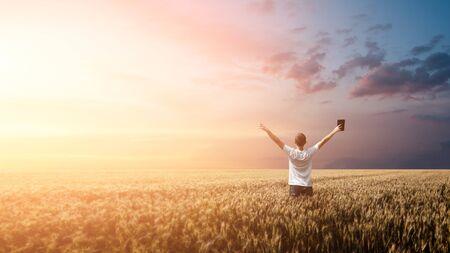 Hombre sujetando la Biblia en un campo de trigo durante el amanecer. tiro panorámico