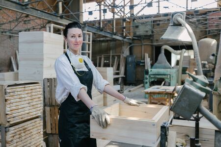 Confident woman working as carpenter in her own woodshop
