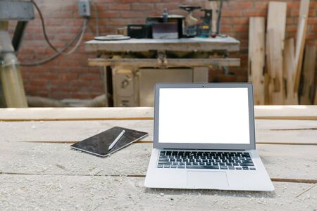 Open laptop in a woodshop with isolated screen on a wooden table