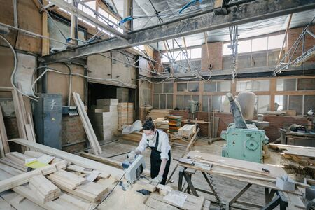 Confident woman working as carpenter in her own woodshop. Carpentry interior