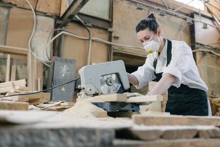 Confident woman working as carpenter in her own woodshop with sawmill