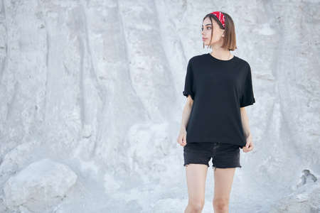Sexy woman or girl wearing black blank t-shirt with space, mock up or design outdoors 免版税图像
