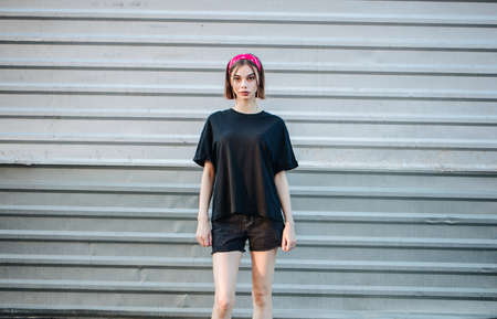 Sexy woman or girl wearing black blank t-shirt with space for your logo, mock up or design in casual urban style 免版税图像