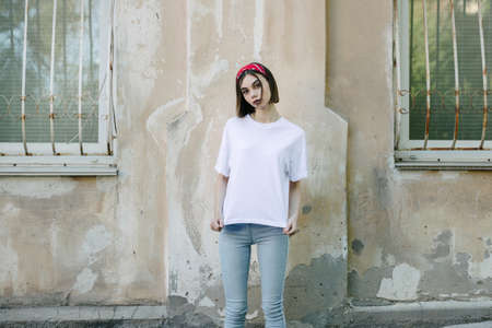 Woman or girl wearing white blank t-shirt with space for your logo, mock up or design in casual urban style 免版税图像